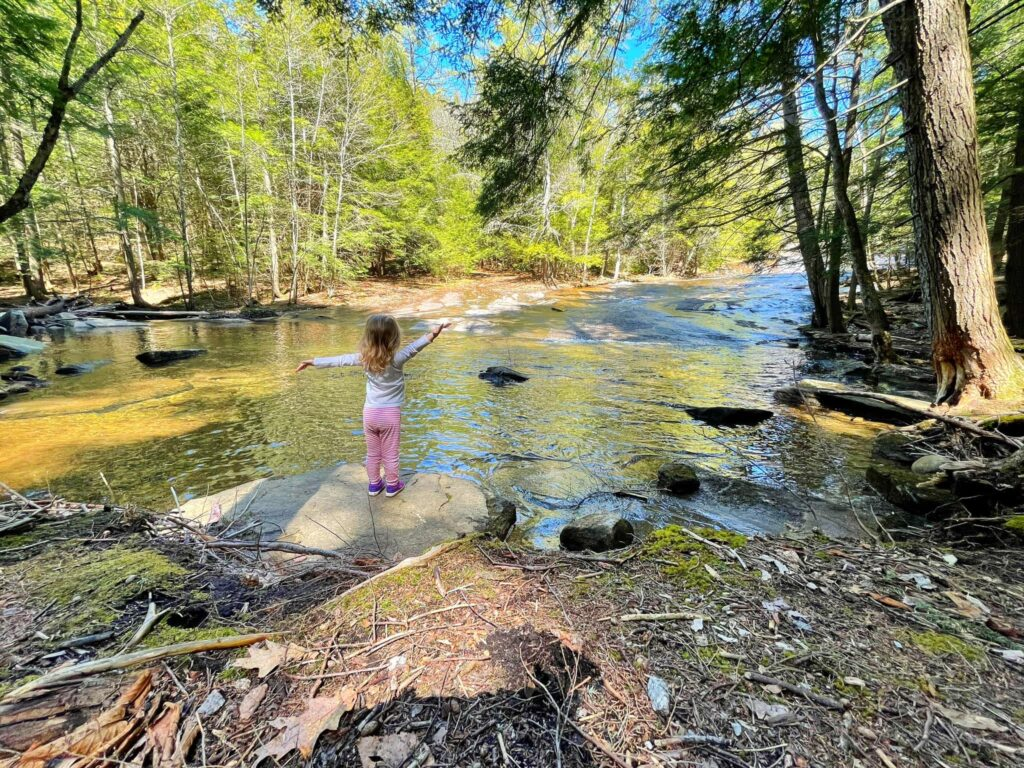 Ellie stands with arms wide open looking out over Bear Slide water, rocks, and trees on a sunny day.