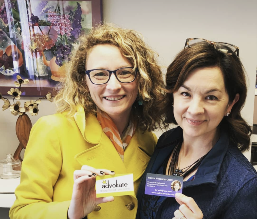 Kate in her yellow coat stands with Wendy in a dark blue blazer. Both are holding their business cards and smiling.